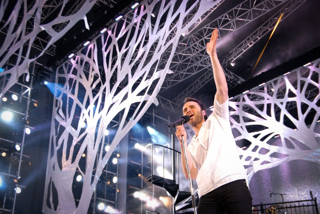 Louis-José Houde sur scène levant le bras au ciel, tournée Les heures verticales.