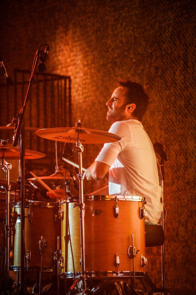 Louis-José Houde de profil jouant de la batterie, tournée Les heures verticales.