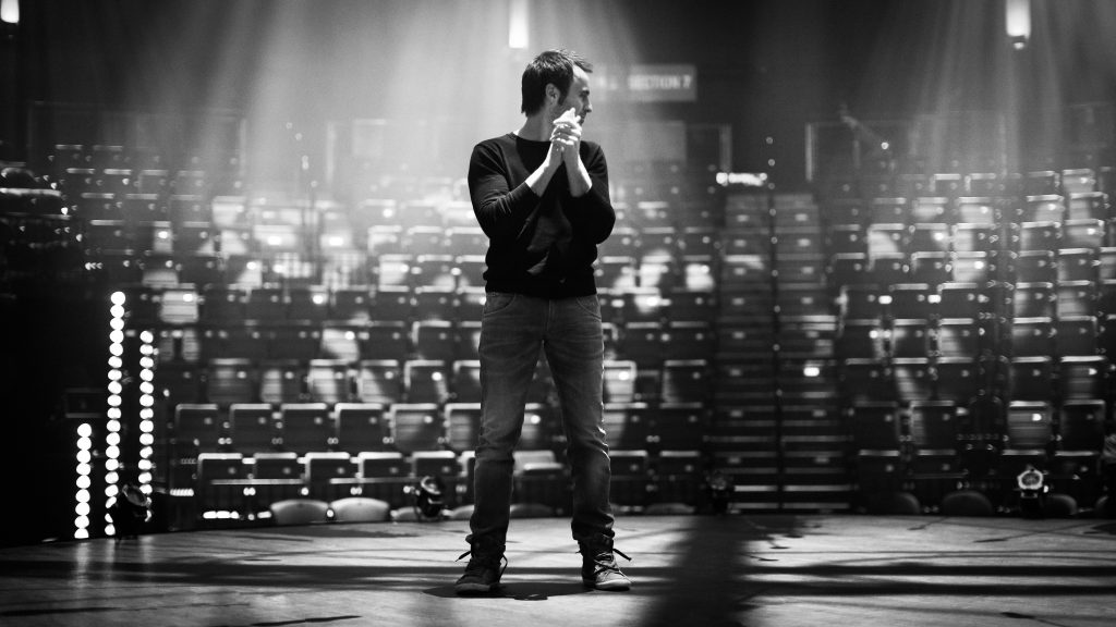 Louis-José Houde sur scène sans spectateurs, noir et blanc, tournée Les heures verticales.