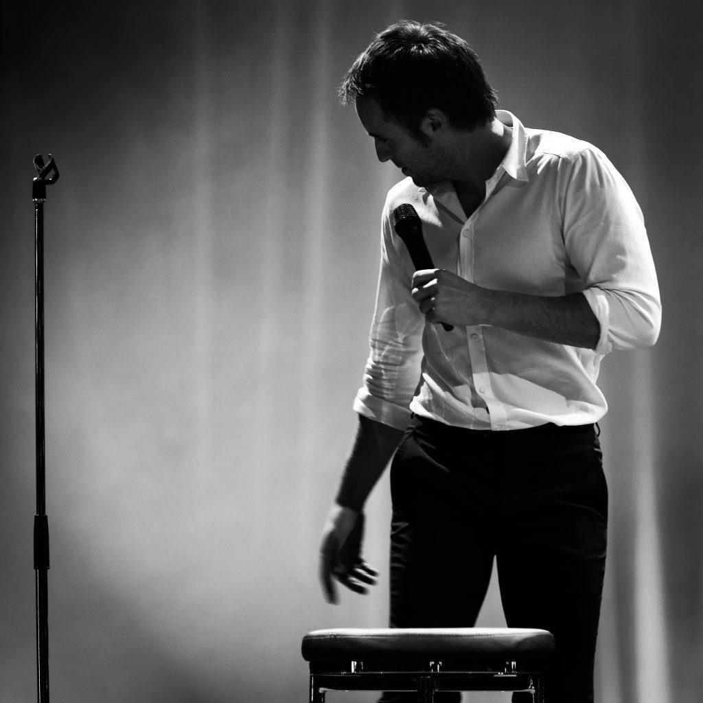 Louis-José Houde sur scène, photo noir et blanc, tournée Les heures verticales.