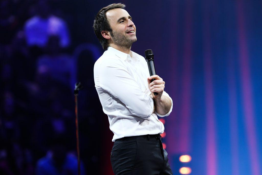 Louis-José Houde bras croisés, souriant au public, tournée Les heures verticales.