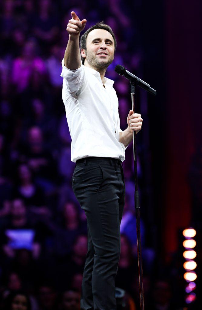 Louis-José Houde au micro pointant le public, tournée Les heures verticales.