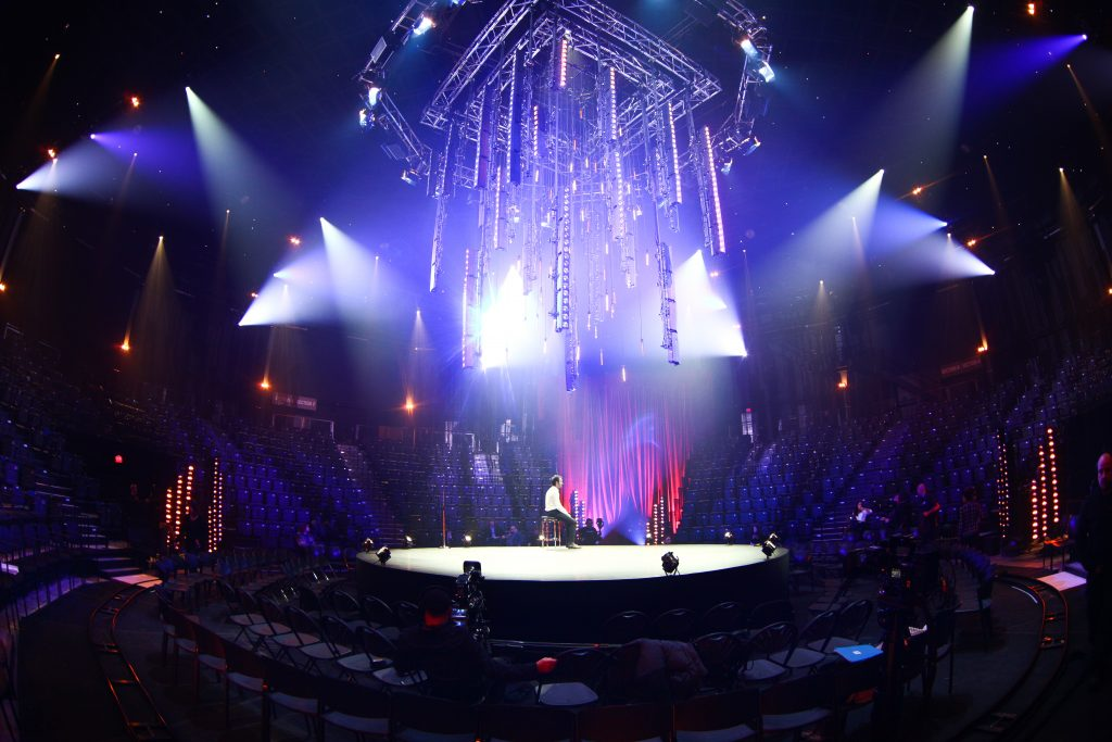 Scène illuminée de Louis-José Houde durant la tournée Les heures verticales