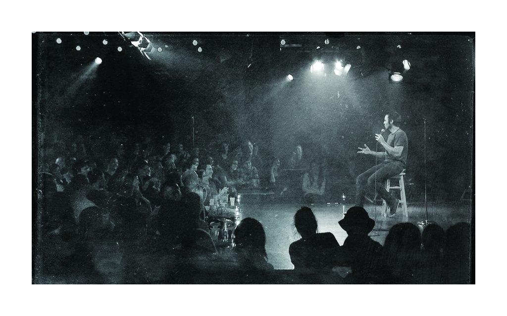Louis-José Houde assis sur scène durant une représentation intimiste du Show caché 2