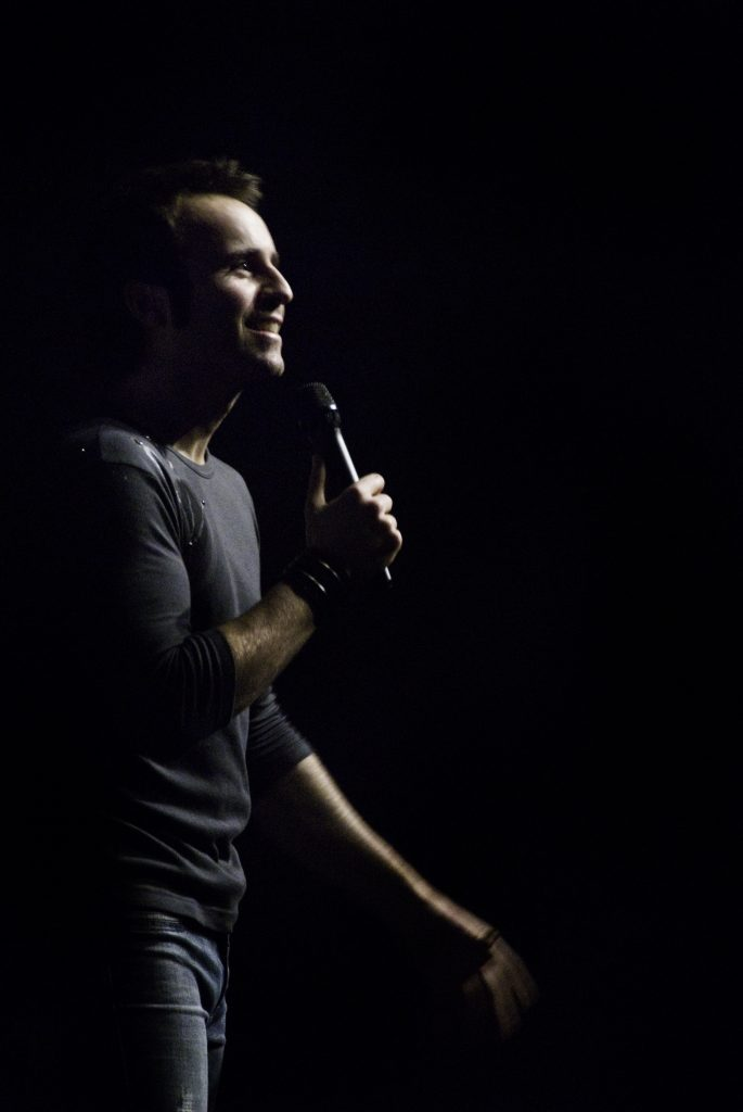 Louis-José Houde performant sur scène dans la noirceur, tournée Suivre la parade.