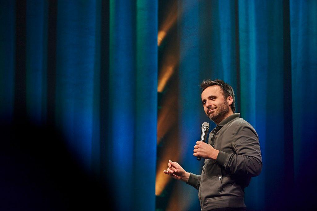 Photo de l'humoriste racontant une anecdote sur scène, tournée Louis-José-Houde préfère novembre.