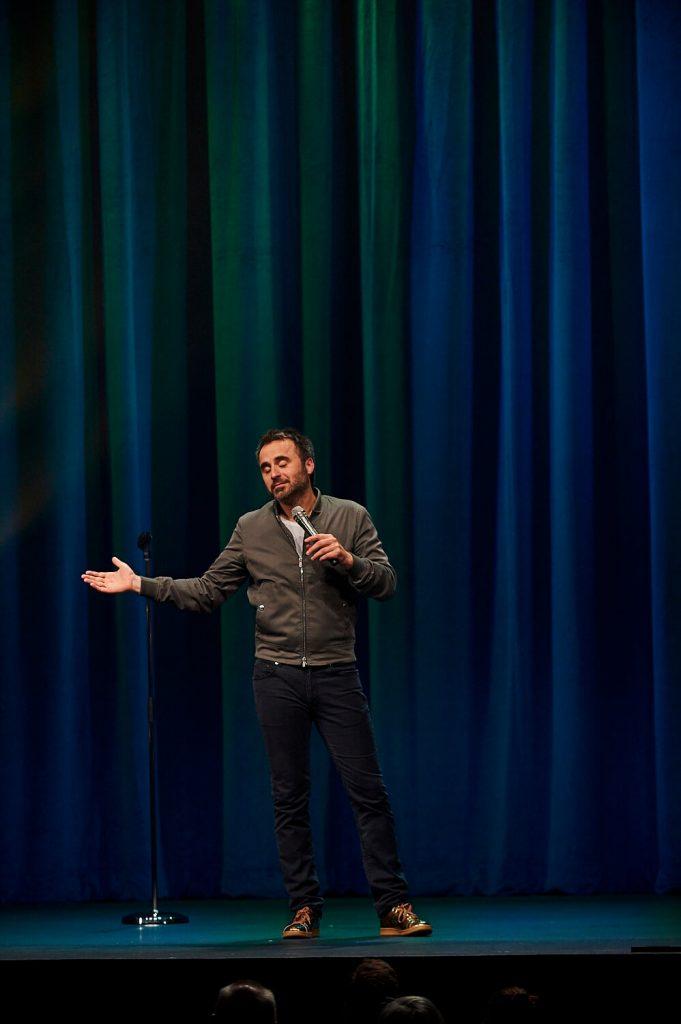 Photo de l'humoriste devant un rideau bleu sur scène, tournée Louis-José-Houde préfère novembre.