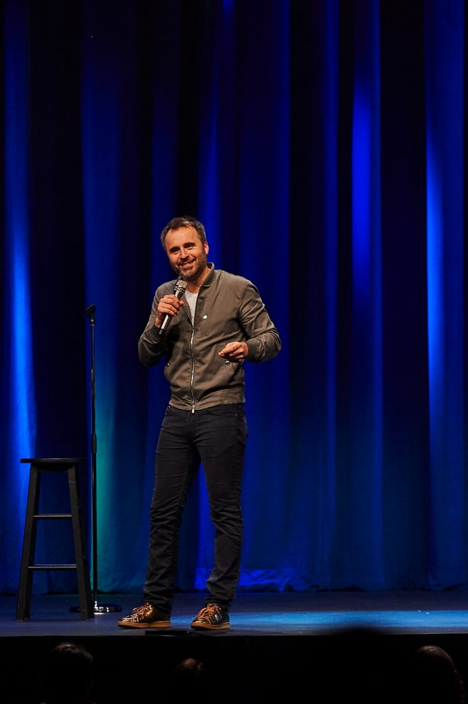 Photo de l'humoriste souriant sur scène, tournée Louis-José-Houde préfère novembre.
