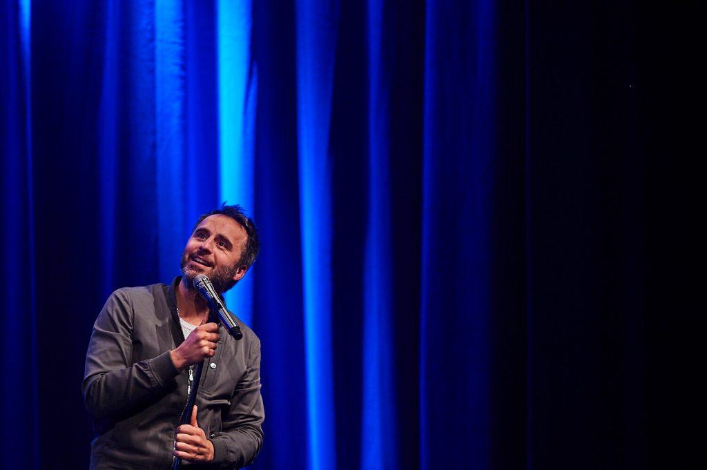 Photo de l'humoriste regardant au loin sur scène, tournée Louis-José-Houde préfère novembre.