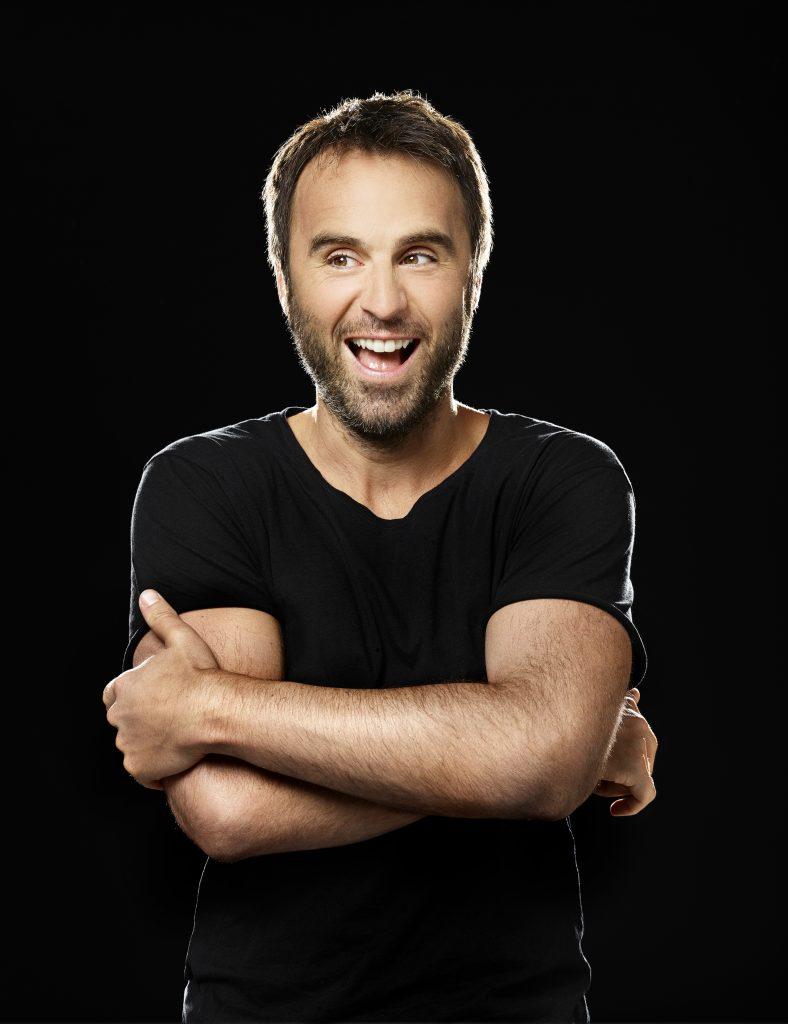 Louis-José Houde bras croisés, souriant sur fond noir, tournée Les heures verticales.