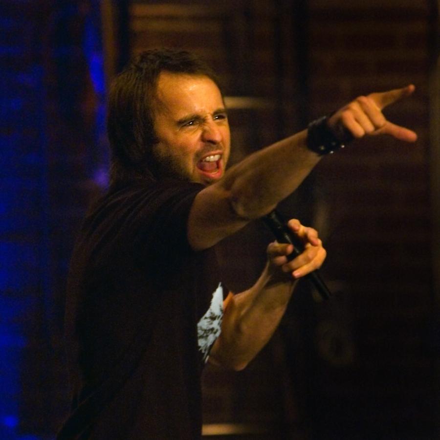 Photo de l'humoriste sur scène pointant le public durant le Show caché 1.