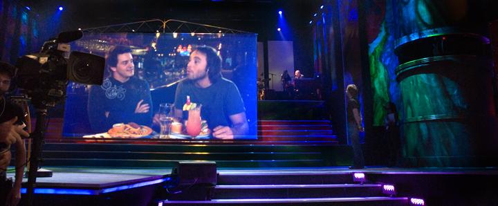 Louis-José Houde sur un écran dans une salle, tournée Suivre la parade.